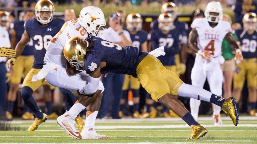 Sep 5, 2015; South Bend, IN, USA; Texas Longhorns quarterback Tyrone Swoopes (18) is tackled by Notre Dame Fighting Irish linebacker Jaylon Smith (9) in the second quarter at Notre Dame Stadium. Mandatory Credit: Matt Cashore-USA TODAY Sports