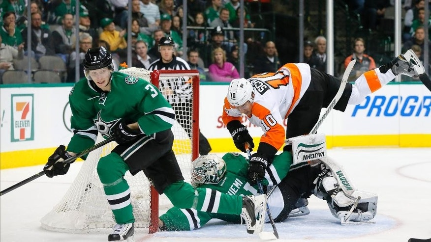 Dallas Stars' John Klingberg (3) of Sweden comes away with the loose puck as goalie Antti Niemi of Finland is knocked over by Philadelphia Flyers center Brayden Schenn (10) in the second period of an NHL hockey game, Friday, Dec. 11, 2015, in Dallas.  Brayden was charged with interference on the play. (AP Photo/Tony Gutierrez)