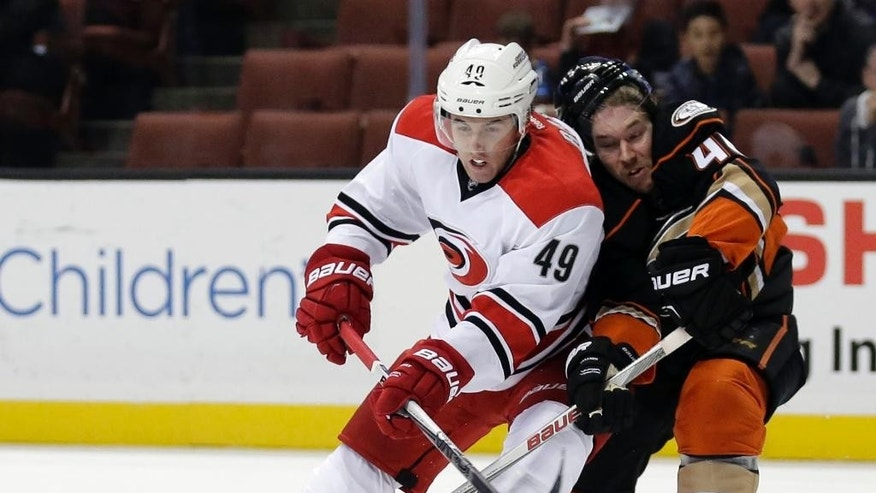 Carolina Hurricanes center Victor Rask, left, battles Anaheim Ducks defenseman Sami Vatanen for the puck during the first period of an NHL hockey game in Anaheim, Calif., Friday, Dec. 11, 2015. (AP Photo/Chris Carlson)
