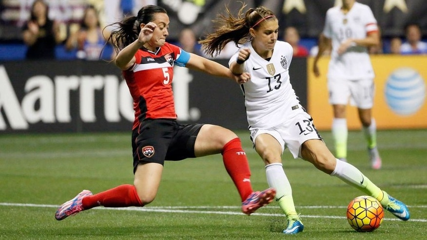 Dec 10, 2015; San Antonio, TX, USA; United States forward Alex Morgan (13) is defended by Trinidad & Tobago defender Arin King (5) during the first half at Alamodome. Mandatory Credit: Soobum Im-USA TODAY Sports