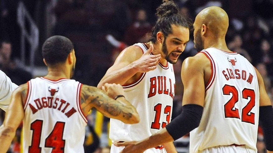 Feb 11, 2014; Chicago, IL, USA; Chicago Bulls point guard D.J. Augustin (14), Chicago Bulls center Joakim Noah (13) and Chicago Bulls power forward Taj Gibson (22) celebrate scoring in the second half against the Atlanta Hawks at the United Center. The Bulls beat the Hawks 100-85. Mandatory Credit: Matt Marton-USA TODAY Sports