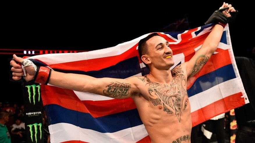 SASKATOON, SK - AUGUST 23: Max Holloway of the United States celebrates after his victory over Charles Oliveira in their featherweight bout during the UFC event at the SaskTel Centre on August 23, 2015 in Saskatoon, Saskatchewan, Canada. (Photo by Jeff Bottari/Zuffa LLC/Zuffa LLC via Getty Images)