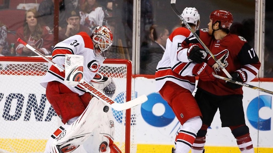 Carolina Hurricanes' Eddie Lack (31), of Sweden, makes a save on a shot as Hurricanes' Noah Hanifin (5) and Arizona Coyotes' Steve Downie (17) watch during the first period of an NHL hockey game Saturday, Dec. 12, 2015 in Glendale, Ariz. (AP Photo/Ross D. Franklin)