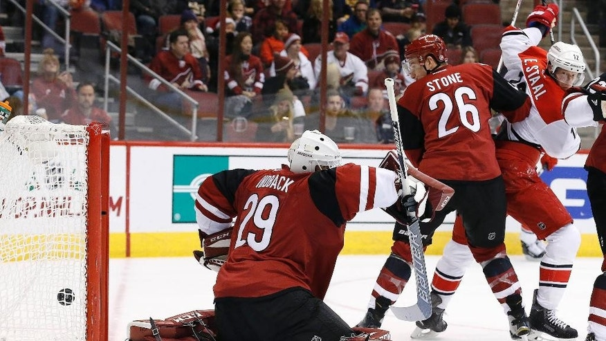 Arizona Coyotes' Anders Lindback (29), of Sweden, gives up a goal to Carolina Hurricanes' Justin Faulk as Hurricanes' Eric Staal (12) and Coyotes' Michael Stone (26) watch during the first period of an NHL hockey game Saturday, Dec. 12, 2015 in Glendale, Ariz. (AP Photo/Ross D. Franklin)