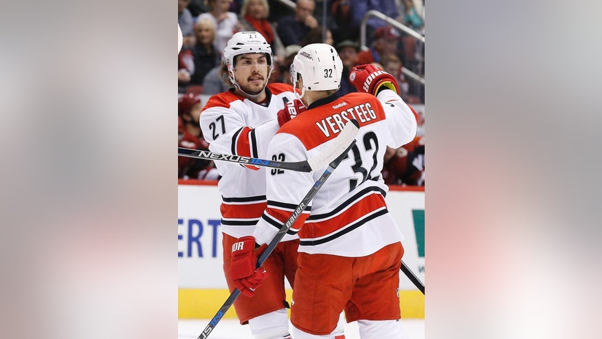 Carolina Hurricanes' Justin Faulk (27) celebrates his goal against the Arizona Coyotes with teammate Kris Versteeg (32) during the first period of an NHL hockey game Saturday, Dec. 12, 2015, in Glendale, Ariz. (AP Photo/Ross D. Franklin)