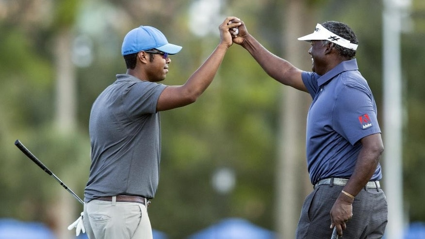 Qass Singh, left and his father Vijay Singh, right celebrate his father's long putt for an eagle on the 18th hole in the first round of the Father/Son Challenge golf tournament in Orlando, Fla., Saturday, Dec. 12, 2015. (AP Photo/Willie J. Allen Jr.)