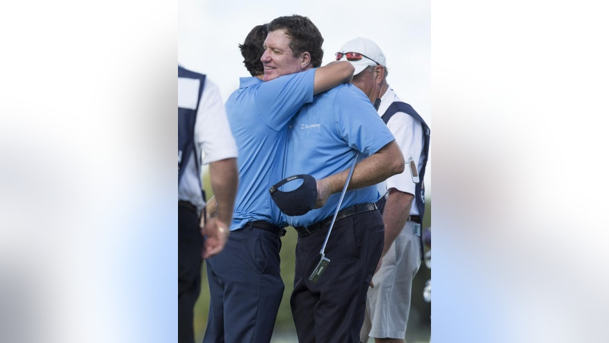Steve Elkington, left, and his father Sam Elkington, right, hug on the 18th hole during the first round of the Father/Son Challenge golf tournament in Orlando, Fla., Saturday, Dec. 12, 2015. (AP Photo/Willie J. Allen Jr.)