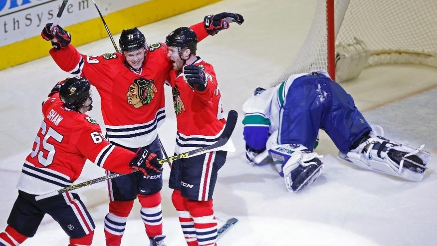 Chicago Blackhawks center Dennis Rasmussen (70) celebrates his goal past Vancouver Canucks goalie Ryan Miller (30) with teammates Andrew Shaw (65) and Bryan Bickell (29) during the third period of an NHL hockey game in Chicago, Sunday, Dec. 13, 2015. Chicago won 4-0. (AP Photo/Andrew A. Nelles)
