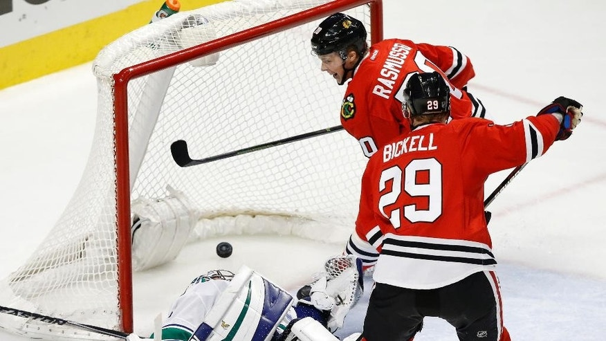 Chicago Blackhawks center Dennis Rasmussen (70) scores past Vancouver Canucks goalie Ryan Miller (30) with left wing Bryan Bickell (29) during the third period of an NHL hockey game in Chicago, Sunday, Dec. 13, 2015. Chicago won 4-0. (AP Photo/Andrew A. Nelles)