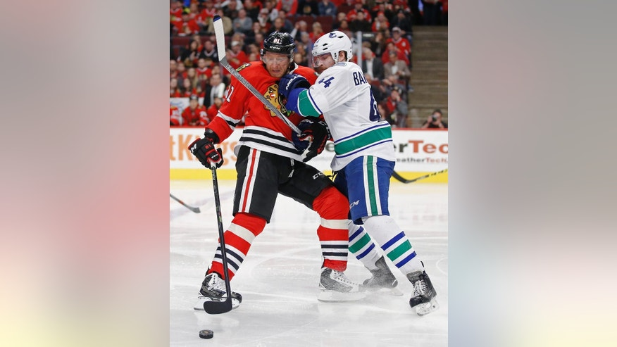 Chicago Blackhawks right wing Marian Hossa (81) and Vancouver Canucks defenseman Matt Bartkowski (44) collide during the second period of an NHL hockey game in Chicago, Sunday, Dec. 13, 2015. (AP Photo/Andrew A. Nelles)