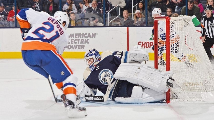 COLUMBUS, OH - DECEMBER 12: Kyle Okposo #21 of the New York Islanders scores the game-winning overtime goal on goaltender Curtis McElhinney #30 of the Columbus Blue Jackets on December 12, 2015 at Nationwide Arena in Columbus, Ohio. New York defeated Columbus 3-2 in overtime. (Photo by Jamie Sabau/NHLI via Getty Images)