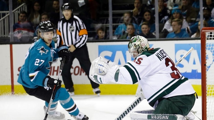 Minnesota Wild goalie Darcy Kuemper, right, blocks a shot next to San Jose Sharks' Joonas Donskoi (27) during the first period of an NHL hockey game Saturday, Dec. 12, 2015, in San Jose, Calif. (AP Photo/Marcio Jose Sanchez)