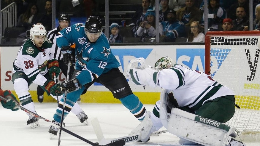 Minnesota Wild goalie Darcy Kuemper, right, stops a shot from San Jose Sharks' Patrick Marleau, center, during the first period of an NHL hockey game Saturday, Dec. 12, 2015, in San Jose, Calif. (AP Photo/Marcio Jose Sanchez)
