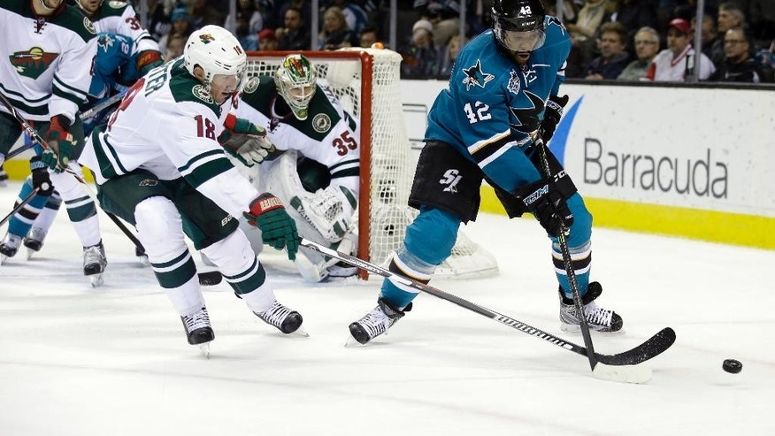 San Jose Sharks' Joel Ward (42) battles with Minnesota Wild's Ryan Carter (18) during the first period of an NHL hockey game Saturday, Dec. 12, 2015, in San Jose, Calif. (AP Photo/Marcio Jose Sanchez)