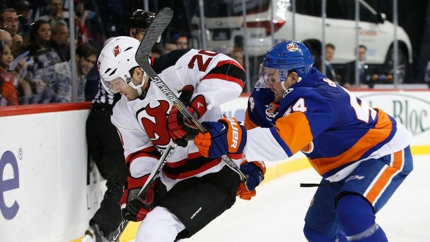 New York Islanders defenseman Calvin de Haan (44) defends against New Jersey Devils right wing Lee Stempniak (20) in the third period of an NHL hockey game in New York, Sunday, Dec. 13, 2015.  The Islanders shut out the Devils 4-0. (AP Photo/Kathy Willens)