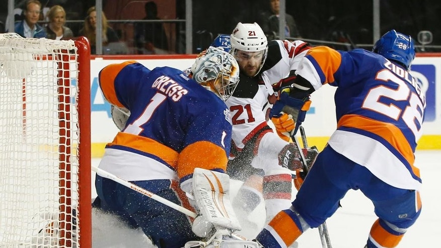 New York Islanders goalie Thomas Greiss (1) and New York Islanders defenseman Marek Zidlicky (28) defend as New Jersey Devils right wing Kyle Palmieri (21) tries to score in the third period of an NHL hockey game in New York, Sunday, Dec. 13, 2015. Zidlicky had two goals as the Islanders shut out the Devils 4-0. (AP Photo/Kathy Willens)