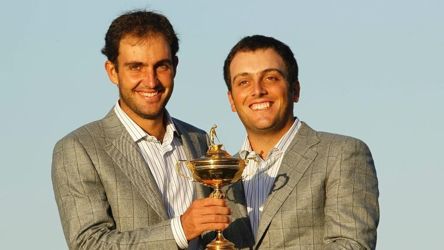 FILE - This is a Monday, Oct.  4, 2010 file photo of Europe's Edoardo Molinari, left, and Francesco Molinari, brothers from Italy, as they hold the trophy after Europe won the 2010 Ryder Cup golf tournament at the Celtic Manor Resort in Newport, Wales. The Ryder Cup is headed to Italy for the first time, with the Marco Simone club in Rome chosen Monday to host golf's biggest team event in 2022. Italy beat rival bids from Germany, Spain and Austria to secure hosting rights for the 44th edition of the biennial competition between Europe and the United States. (AP Photo/Jon Super, File)