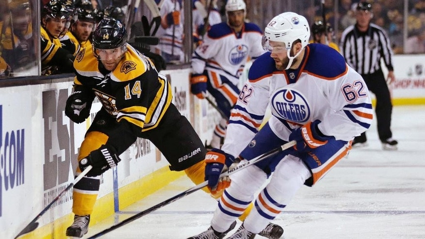 Edmonton Oilers defenseman Eric Gryba (62) strips the puck away from Boston Bruins right wing Brett Connolly (14) during the second period of an NHL hockey game in Boston, Monday, Dec. 14, 2015. (AP Photo/Charles Krupa)