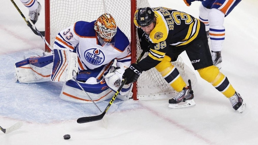 Edmonton Oilers goalie Cam Talbot (33) knocks the puck away on a shot by Boston Bruins left wing Matt Beleskey (39) during the first period of an NHL hockey game in Boston, Monday, Dec. 14, 2015. (AP Photo/Charles Krupa)