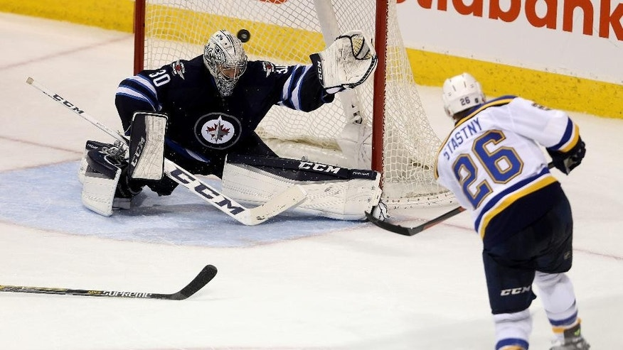 St. Louis Blues' Paul Stastny (26) scores on Winnipeg Jets goalie Connor Hellebuyck (30) during the third period of an NHL hockey game Tuesday, Dec. 15, 2015, in Winnipeg, Manitoba. (Trevor Hagan/The Canadian Press via AP)