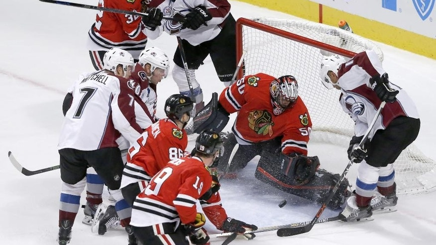 Chicago Blackhawks goalie Corey Crawford (50) makes a save on a shot from Colorado Avalanche right wing Jarome Iginla, right, during the first period of an NHL hockey game Tuesday, Dec. 15, 2015, in Chicago. (AP Photo/Charles Rex Arbogast)