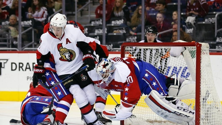 Washington Capitals goalie Braden Holtby (70) uses his body to shove Ottawa Senators center Kyle Turris (7) out of the way during the second period of an NHL hockey game Wednesday, Dec. 16, 2015, in Washington. (AP Photo/Alex Brandon)