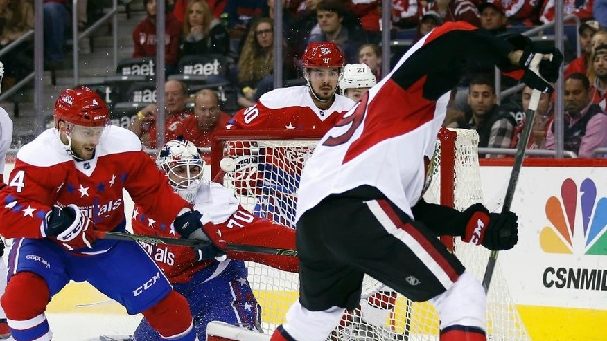 Ottawa Senators left wing David Dziurzynski, right, tries to shoot a rebound past Washington Capitals goalie Braden Holtby (70), with Capitals defenseman Taylor Chorney (4) helping Holtby, during the second period of an NHL hockey game Wednesday, Dec. 16, 2015, in Washington. (AP Photo/Alex Brandon)