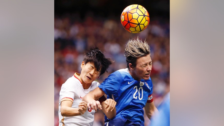 U.S. forward Abby Wambach (20) heads the ball on a  corner kick as China's Wang Shanshan defends during the first period of an international friendly soccer match against China in New Orleans, Wednesday, Dec. 16, 2015. Wambah was playing in her final international match. (AP Photo/Gerald Herbert)