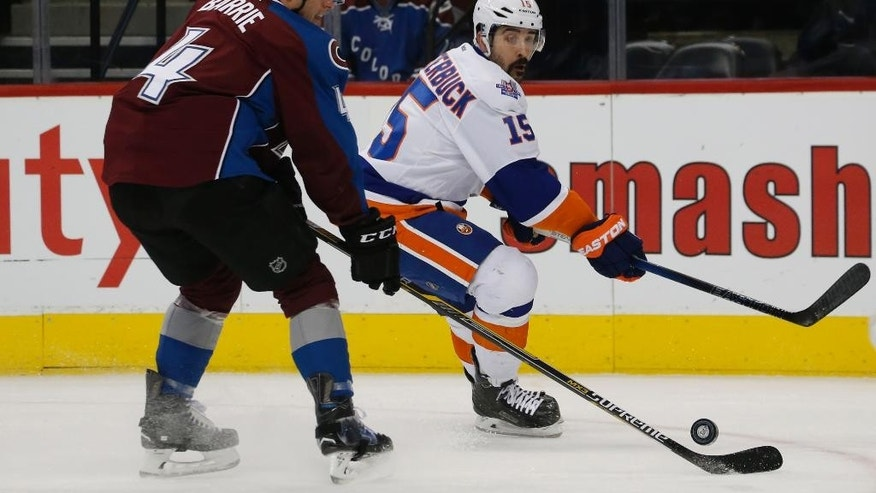 New York Islanders right wing Cal Clutterbuck, back, loses control of the puck to Colorado Avalanche defenseman Tyson Barrie in the first period of an NHL hockey game, Thursday, Dec.17, 2015, in Denver. (AP Photo/David Zalubowski)