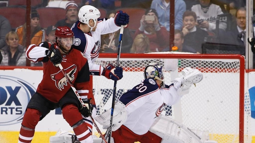 Columbus Blue Jackets' Curtis McElhinney (30) gives up a goal to Arizona Coyotes' Antoine Vermette as Coyotes' Tobias Rieder, left, battles Blue Jackets' Dalton Prout, second from left, during the first period of an NHL hockey game, Thursday, Dec. 17, 2015, in Glendale, Ariz. (AP Photo/Ross D. Franklin)