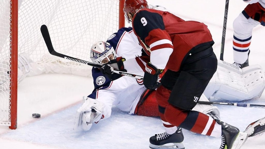 Arizona Coyotes' Viktor Tikhonov (9), of Russia, beats Columbus Blue Jackets' Curtis McElhinney, left, for a goal during the second period of an NHL hockey game, Thursday, Dec. 17, 2015, in Glendale, Ariz. (AP Photo/Ross D. Franklin)
