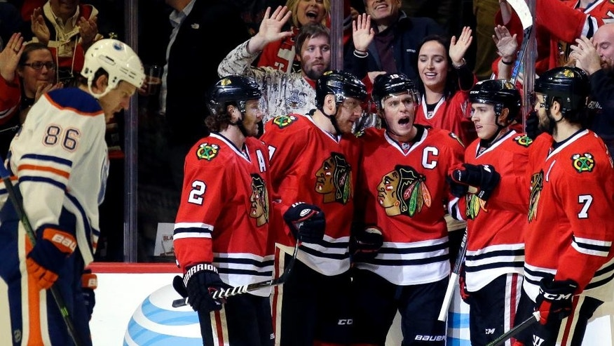Chicago Blackhawks center Jonathan Toews, third from right, celebrates with defenseman Duncan Keith (2), right wing Marian Hossa (81), center Teuvo Teravainen (86) and defenseman Brent Seabrook (7) after scoring his goal as Edmonton Oilers defenseman Nikita Nikitin, left, looks down during the first period of an NHL hockey game Thursday, Dec. 17, 2015, in Chicago. (AP Photo/Nam Y. Huh)