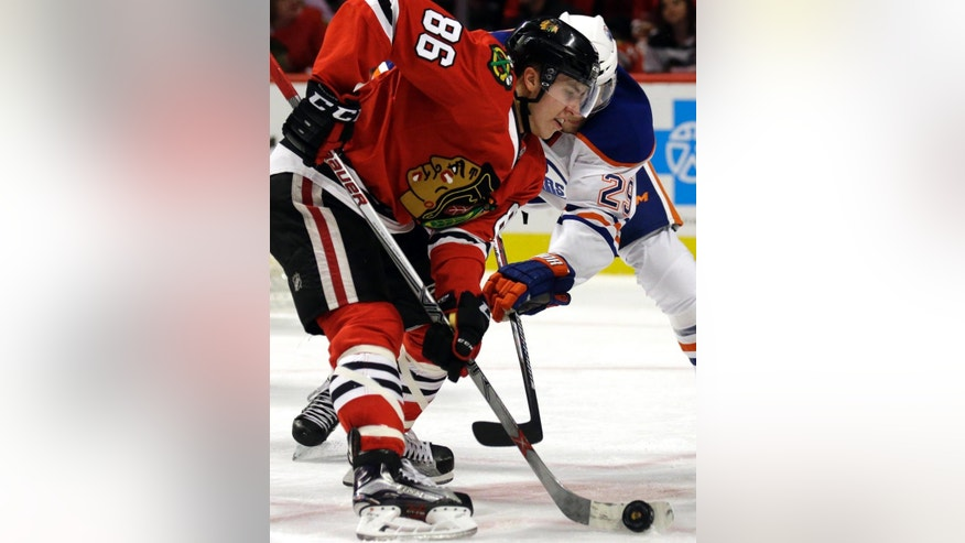 Chicago Blackhawks center Teuvo Teravainen (86) controls the puck against Edmonton Oilers center Leon Draisaitl during the second period of an NHL hockey game Thursday, Dec. 17, 2015, in Chicago. (AP Photo/Nam Y. Huh)