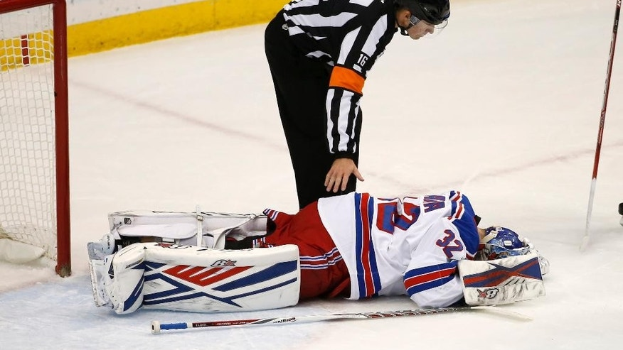 Official Brian Pochmara checks on New York Rangers goalie Antti Raanta after Raanta took a puck to the forehead during the first period of an NHL hockey game against the Minnesota Wild in St. Paul, Minn., Thursday, Dec. 17, 2015. Raanta left the game. (AP Photo/Ann Heisenfelt)