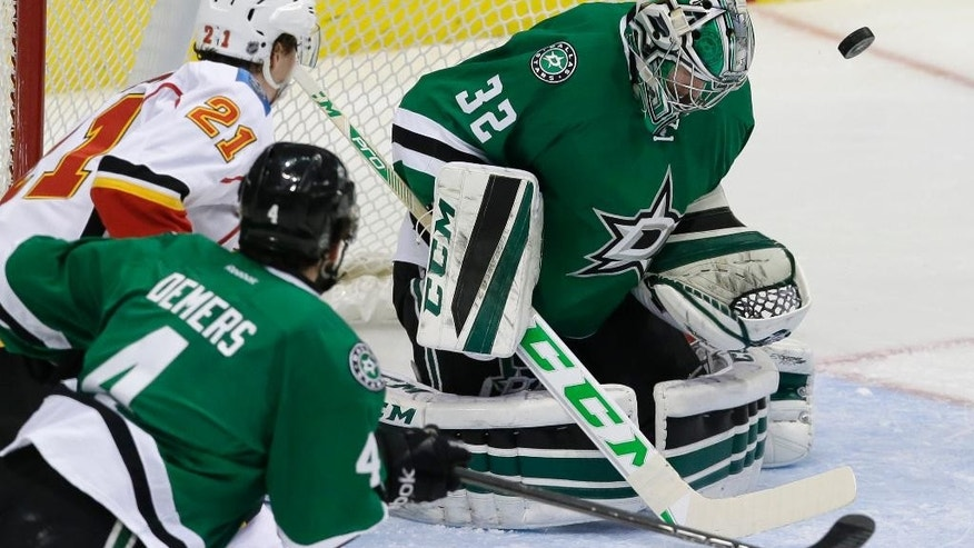 Dallas Stars goalie Kari Lehtonen (32) deflects a shot as teammate Jason Demers (4) and Calgary Flames left wing Mason Raymond (21) watch during the second period of an NHL hockey game Thursday, Dec. 17, 2015, in Dallas. (AP Photo/LM Otero)