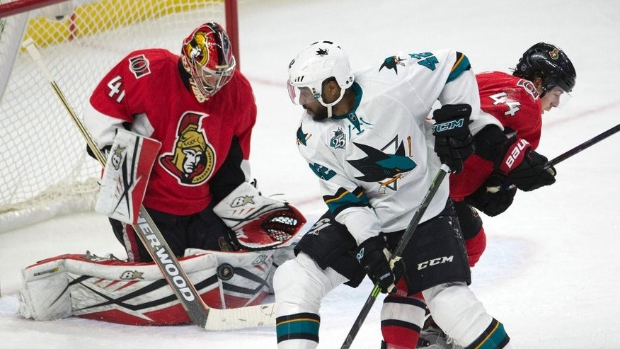 Ottawa Senators goalie Craig Anderson, left, makes a save as San Jose Sharks right wing Joel Ward, center, battles in front of the net with Senators center Jean-Gabriel Pageau during second-period NHL hockey game action Friday, Dec. 18, 2015, in Ottawa, Ontario. (Adrian Wyld/The Canadian Press via AP) MANDATORY CREDIT