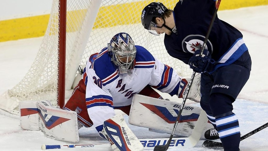 New York Rangers goaltender Henrik Lundqvist (30) stops Winnipeg Jets' Jacob Trouba (8) during the first period of an NHL hockey game Friday, Dec. 18, 2015, in Winnipeg, Manitoba. (Trevor Hagan/The Canadian Press via AP)