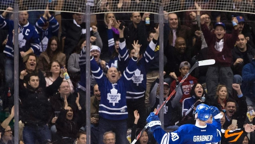 Toronto Maple Leafs' Michael Grabner celebrates with fans after scoring against Los Angeles Kings during the third period of an NHL hockey game Saturday, Dec. 19, 2015, in Toronto, (Chris Young/The Canadian Press via AP)