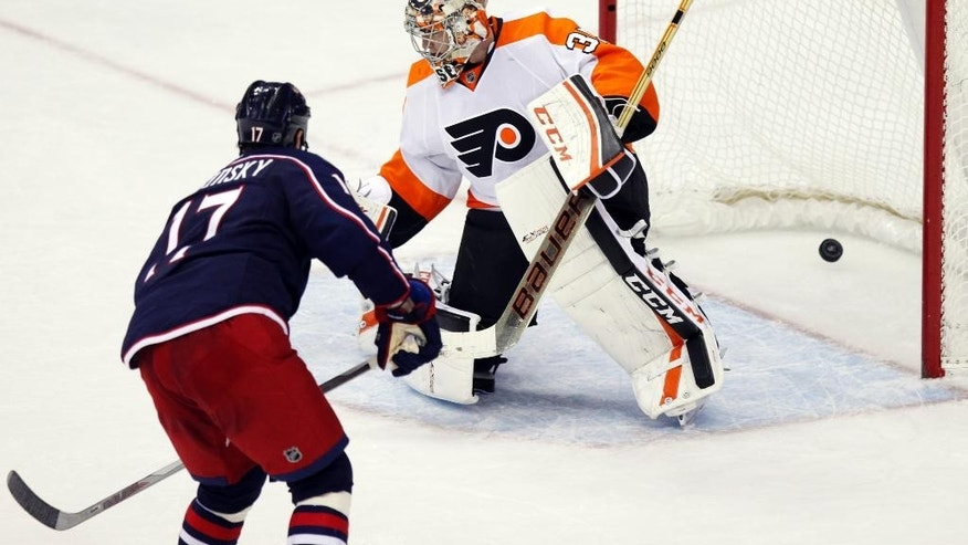 Columbus Blue Jackets' Brandon Dubinsky, left, scores against Philadelphia Flyers' Steve Mason in a shoot out during an NHL hockey game in Columbus, Ohio, Saturday, Dec. 19, 2015. The Blue Jackets won 3-2. (AP Photo/Paul Vernon)
