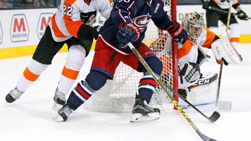 Columbus Blue Jackets' Boone Jenner (38), center, works for the puck between Philadelphia Flyers' Luke Schenn (22), left, and goalie Steve Mason (35) during the second period of an NHL hockey game in Columbus, Ohio, Saturday, Dec. 19, 2015. (AP Photo/Paul Vernon)
