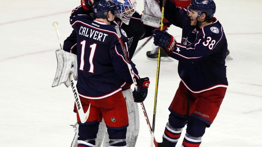Columbus Blue Jackets' Matt Calvert, left, goalie Joonas Korpisalo, of Finland, and Boone Jenner celebrate after Korpisalo stopped a shot by Philadelphia Flyers' Brayden Schenn in a shoot out during an NHL hockey game in Columbus, Ohio, Saturday, Dec. 19, 2015. The Blue Jackets won 3-2. (AP Photo/Paul Vernon)