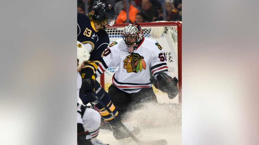 Buffalo Sabres center Tyler Ennis (63) follows a rebound from Chicago Blackhawks goaltender Corey Crawford (50) during the first period of an NHL hockey game, Saturday Dec. 19, 2015 in Buffalo, N.Y. (AP Photo/Gary Wiepert)