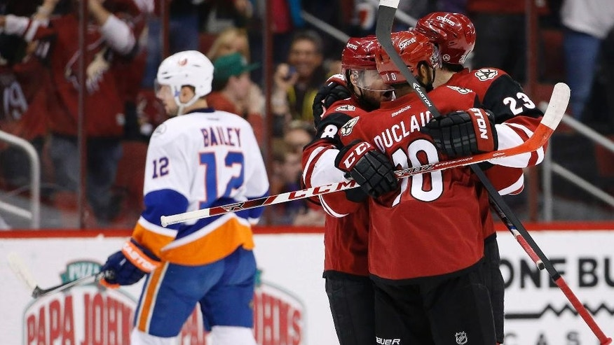 Arizona Coyotes' Oliver Ekman-Larsson (23), of Sweden, celebrates his goal against the New York Islanders with Anthony Duclair (10) and Tobias Rieder (8), of Germany, as Islanders' Josh Bailey (12) skates away during the first period of an NHL hockey game Saturday, Dec. 19, 2015, in Glendale, Ariz. (AP Photo/Ross D. Franklin)