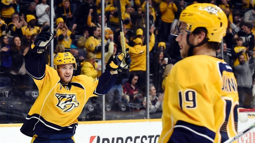 Nashville Predators left wing Viktor Arvidsson, left, and center Calle Jarnkrok (19), both from Sweden, celebrate after teammate James Neal scored a goal against the Minnesota Wild in the second period of an NHL hockey game Saturday, Dec. 19, 2015, in Nashville, Tenn. (AP Photo/Mark Zaleski)