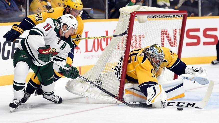 Nashville Predators goalie Pekka Rinne (35), of Finland, blocks a shot by Minnesota Wild left wing Zach Parise (11) as Predators defenseman Roman Josi (59), of Switzerland, defends in the first period of an NHL hockey game Saturday, Dec. 19, 2015, in Nashville, Tenn. (AP Photo/Mark Zaleski)