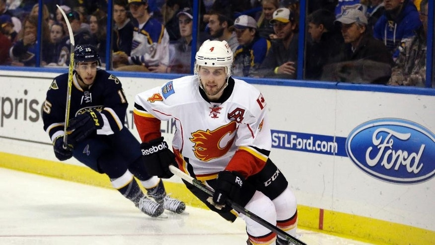 Calgary Flames' Kris Russell, right, controls the puck as St. Louis Blues' Robby Fabbri gives chase during the second period of an NHL hockey game Saturday, Dec. 19, 2015, in St. Louis. (AP Photo/Jeff Roberson)