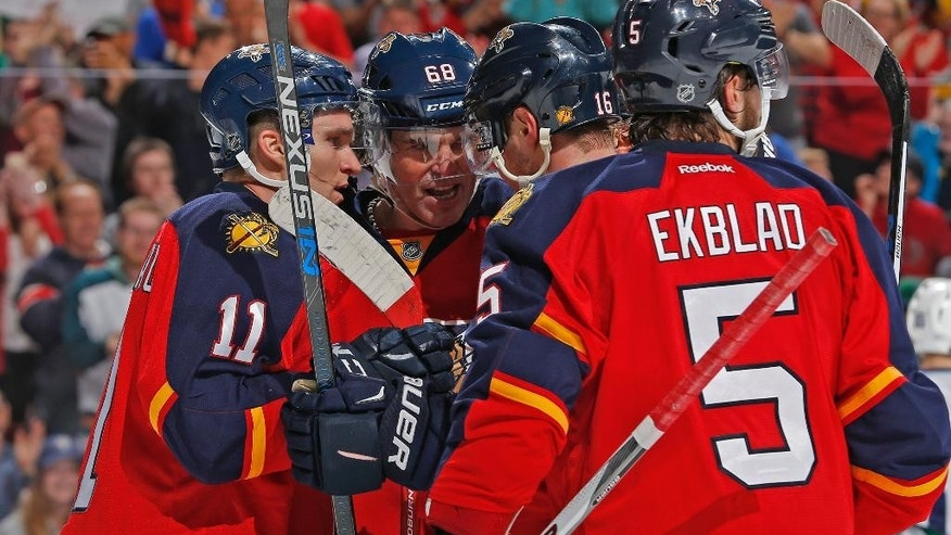 Florida Panthers forward Jaromir Jagr (68) is congratulated by forward Aleksander Barkov (16) and forward Jonathan Huberdeau (11) after scoring the go-ahead goal during the first period of an NHL hockey game against the Vancouver Canucks, Sunday, Dec. 20, 2015, in Sunrise, Fla. (AP Photo/Joel Auerbach)
