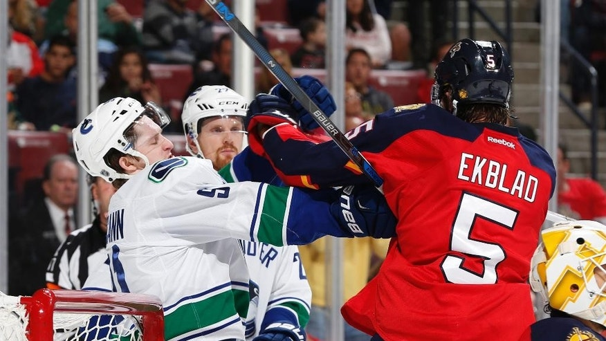 Vancouver Canucks center Jared McCann (91) and Florida Panthers defenseman Aaron Ekblad (5) tangle at the side of the net during the second period of an NHL hockey game, Sunday, Dec. 20, 2015, in Sunrise, Fla. (AP Photo/Joel Auerbach)