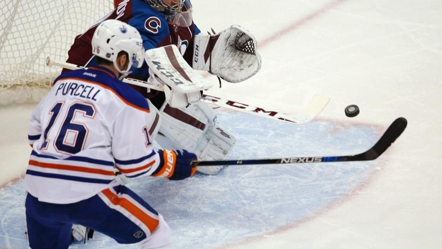 Colorado Avalanche goalie Semyon Varlamov, back, of Russia, makes a stick save of a redirected shot by Edmonton Oilers right wing Teddy Purcell during the first period of an NHL hockey game Saturday, Dec. 19, 2015, in Denver. (AP Photo/David Zalubowski)