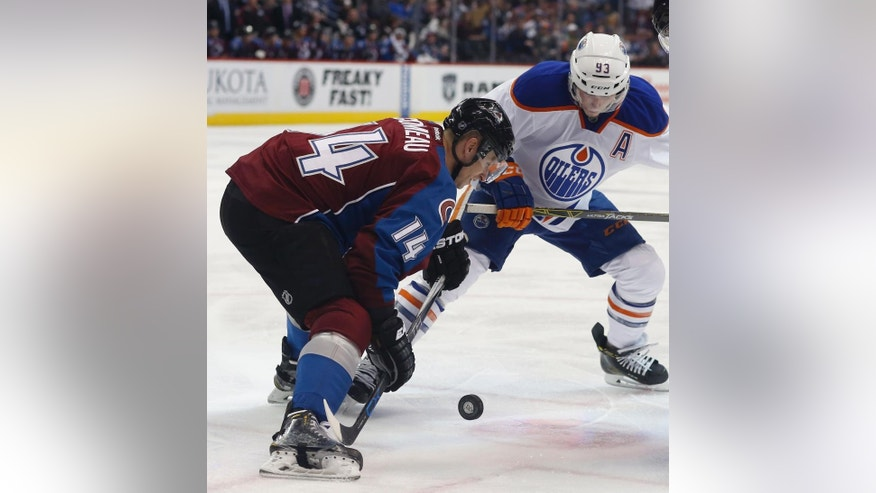 Colorado Avalanche left wing Blake Comeau, left, battles for control of the puck with Edmonton Oilers center Ryan Nugent-Hopkins during the third period of an NHL hockey game Saturday, Dec. 19, 2015, in Denver. (AP Photo/David Zalubowski)